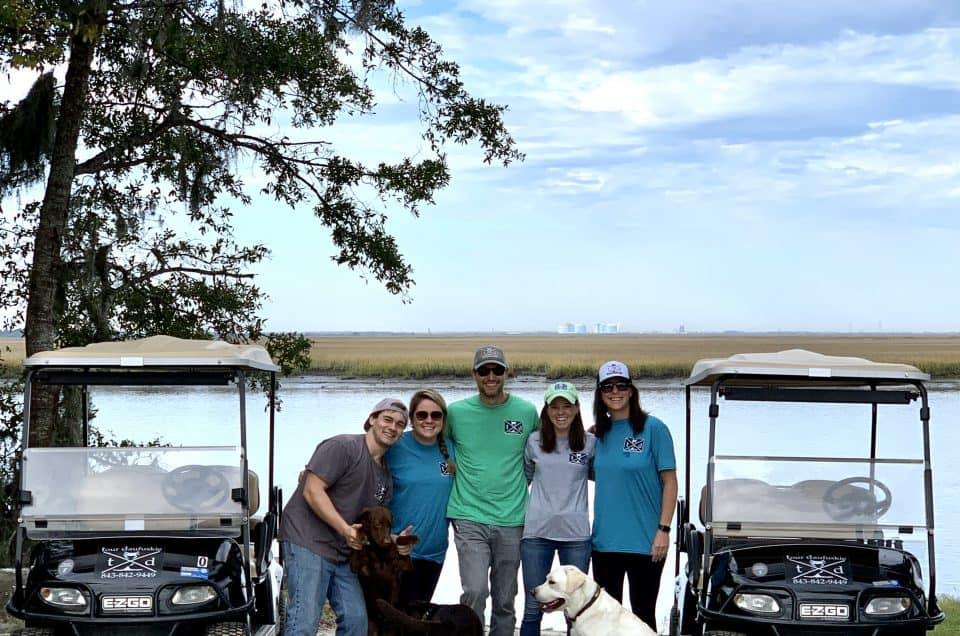 Tour Daufuskie's employees standing next to golf cart rentals